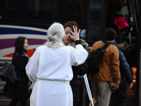 Kerr imposes ashes on Ash Wednesday to a commuter, just before she steps onto a NJ Transit bus headed for New York City.
