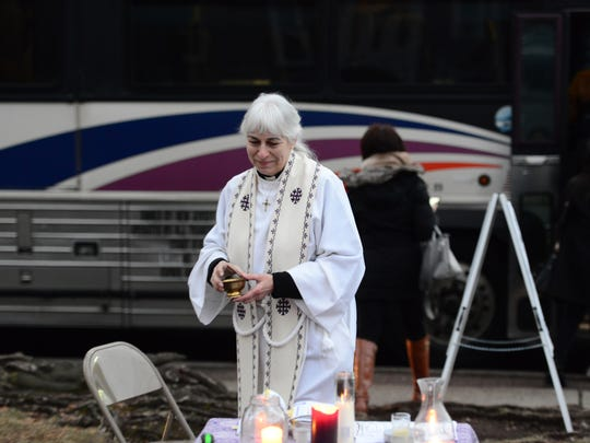 Rev. Susan Kerr, of The Old North Reformed Church, set up an area to impose ashes on Ash Wednesday to commuters at a bus stop in front of her church in Dumont Wednesday morning February 14, 2018.