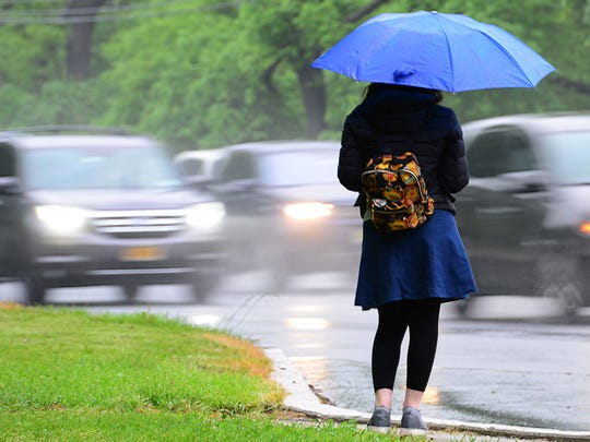 A woman uses an umbrella to shield herself from the rain as she waits for her ride along Route 4 westbound in Teaneck on Thursday May 17, 2018.