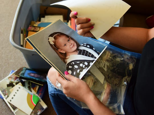 Amanda Zita looks through childhood pictures of herself at her home in Wanaque.