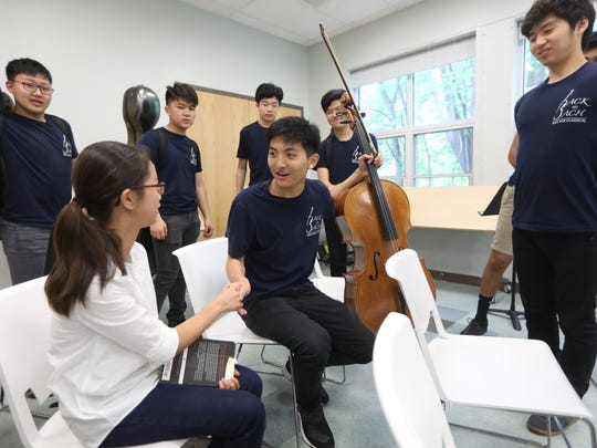 Lee exchanges greetings with Iris Sung 12, of Tenafly, after a Back to Bach performance at the Haworth Public Library in May.