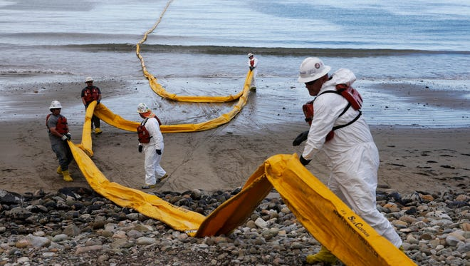 FILE - In this May 21, 2015, file photo, workers prepare an oil containment boom at Refugio State Beach, north of Goleta, Calif. The shutdown of a pipeline that spilled up to 101,000 gallons of crude on the Santa Barbara coast forced Exxon Mobil Corp. to halt operations at three offshore platforms because it couldn't deliver oil to refineries, the company said Tuesday, June 23. (AP Photo/Jae C. Hong, File)