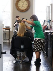 Owner Hillary Diehl and stylist Amanda Doyle work with clients on Thursday at Salon Vivace on Fourth Street in downtown Mansfield.