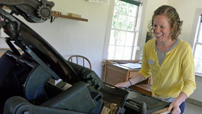 Amy Meyer, Manitowoc County Historical Society executive director, demonstrates a printing press at Pinecrest Historical Village's print shop.