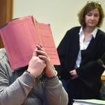 Former nurse, only identified as Niels H., hides his face behind a folder next to his lawyer, Ulrike Baumann, at the local court in Oldenburg, Germany, Thursday, Feb. 26, 2015. The court found the 38-year-old guilty of charges including two counts of murder, and two counts of attempted murder and sentenced him to life in prison.