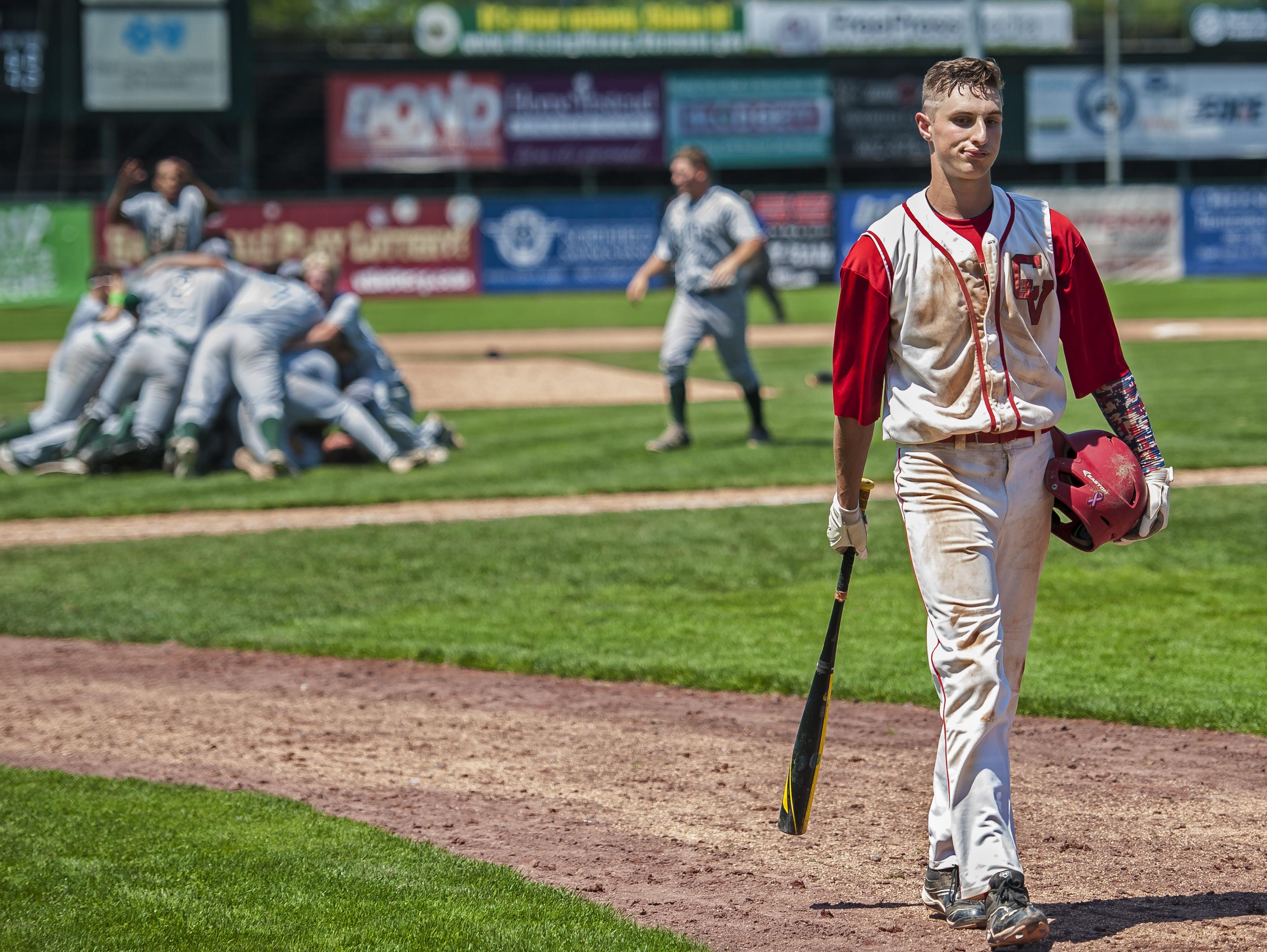 CVU's Rayne Supple, right, walks away after striking out in extra innings to end the Division I state high school baseball championship against Rice at Centennial Field in Burlington on Saturday, June 13, 2015.