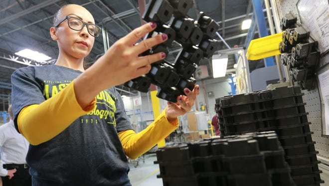 Judith Verdim inspects a plastic molding before placing it in a box for shipment last week at the Plastic Molding Technology factory in East El Paso.