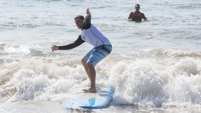 Sports writer Ryan Marshall learns how to surf using a soft-top surfboard under the instruction of Colin Herlihy in Ocean City.