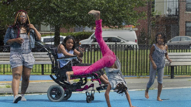 Yesenia Park watches as her sisters and cousins do cartwheels as they play under the water spray at Audubon Park in Jersey City. Yesenia Parker of Camden was shot by her father who was sentenced to 60 years in prison last month. Her mother Shandar moved the family to Jersey City to try to start over.
