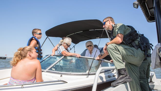 Maryland Natural Resources Police officer, Corporal Brad Bunting, speaks to a family of boaters after being stopped for not properly displaying their registration. The officers also check all boats for the proper safety gear every time they stop a vehicle.
