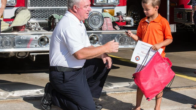 Ocean City Fire Department Chief Chris Larmore awards Mason Farr, 7, of Ocean City a fire chief's badge during a ceremony in his honor at the department's headquarters on Monday. Farr is being recognized for helping his aunt after she suffered a spinal cord injury on a water slide.