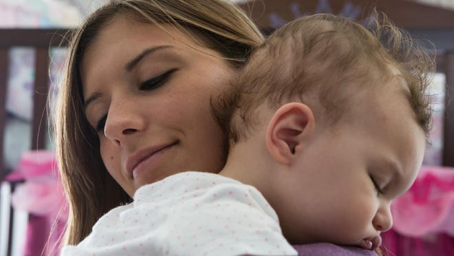 Alexa Shoultes, of Frankford, holds her daughter Alana Prettyman, 1, at their home Wednesday.
