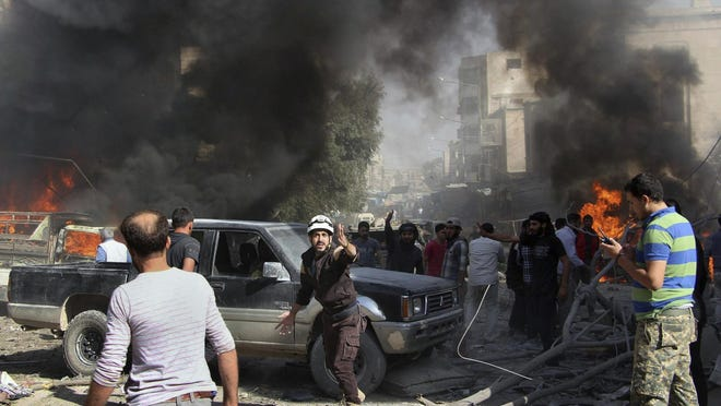 In this Oct. 8, 2017 file photo provided by the Syrian Civil Defense White Helmets, Civil Defense workers and Syrian citizens gather after an airstrike hit a market in Maaret al-Numan in southern Idlib, Syria.