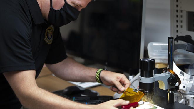 Detective Sgt. Dave Kohler demonstrates a chip-off extraction, a last resort method used to retrieve data at the expense of the rest of the phone, at the High-Tech Crimes Unit of the Burlington County Prosecutor's Office in Pemberton.