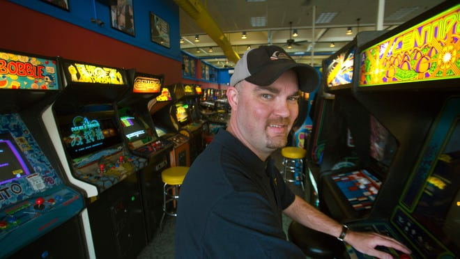 Ken Kalada plays Centipede, one of the many arcade games available at his Red Bank business, Yestercades.