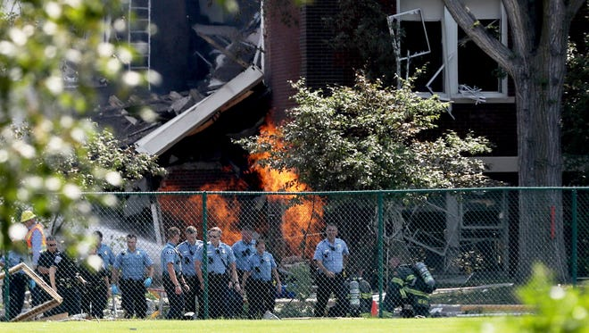 Emergency personnel move away as a gas fire continues to burn following an explosion at Minnehaha Academy.