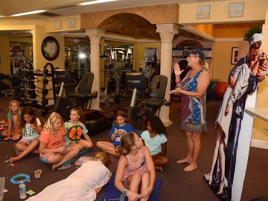 "Lois Bolin speaks to the kids as they work surrounded by exercise equipment at Addicted to Fitness. A group of children worked on making rubber band ""loom"" bracelets for the veterans being honored at the Greatest Generation Breakfast on August 13."