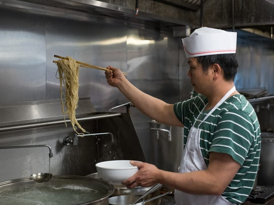 Head chef Baojiang Li inspects the noodles as they come out of the water.