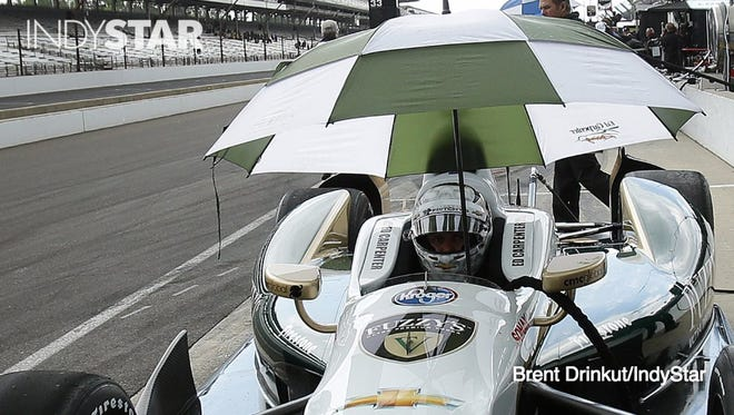 Driver Ed Carpenter sits with a umbrella in his car May 16, 2014, as rains move in during practice for the Indy 500 at Indianapolis Motor Speedway.