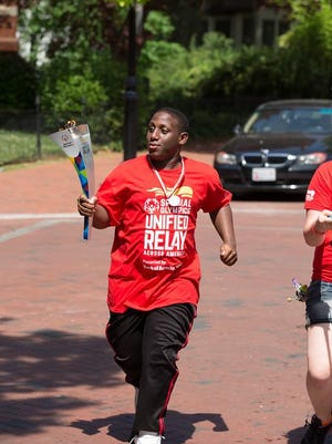 Pocomoke High School student and unified athlete Andre Collins runs with the torch during the Special Olympics Torch Run.