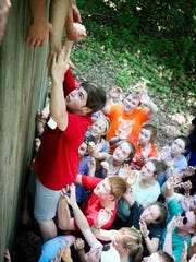 Alex Close, a student from Northern Ireland, scales a wall as part of team-building exercises.