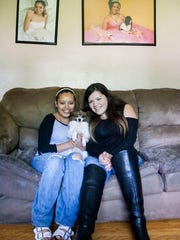 Ixayana Gonzales, 19, left, and Alondra Hernandez, 17, mix Hispanic culture with American lives. Portraits from their quinceañeras hang in their living room in this photo taken July 21.