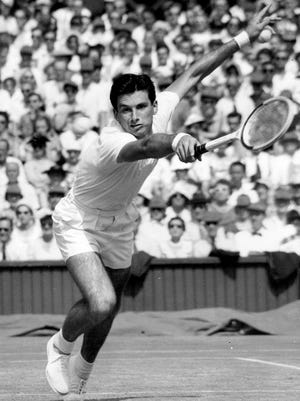 From July 3, 1957, Australian tennis player Ashley Cooper leans forward to return service during his two-hour match against compatriot Neale Fraser at Wimbledon. Cooper, who won four Grand Slam singles titles including the Australian, Wimbledon and U.S. championships in 1958, has died. He was 83. Tennis Australia said Friday, May 22, 2020, that the former No. 1-ranked player and long-time administrator had died after a long illness.