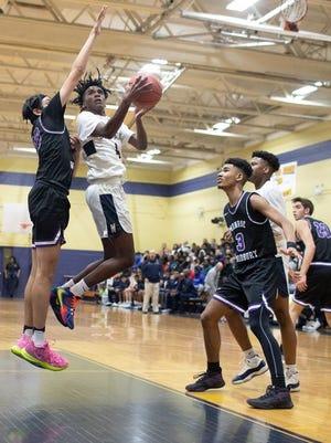Newburgh Free Academy's Jah'Likai King, center, drives the basket again Monroe-Woodbury on Feb. 12, 2020.