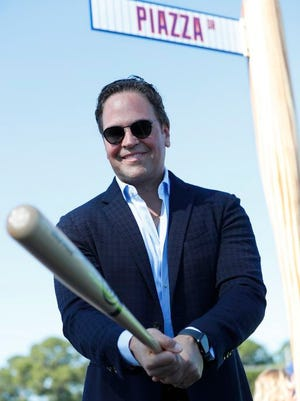 Former New York Mets catcher Mike Piazza poses for a photo under a street sign for the newly named Piazza Dr., after a ceremony in front of the Mets spring training facility, Thursday, Jan. 16, 2020, in Port St. Lucie, Fla.