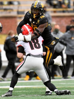 Missouri defensive lineman Trajan Jeffcoat, top, sacks Georgia quarterback JT Daniels during the first half of an NCAA college football game Saturday, Dec. 12, 2020, in Columbia, Mo.