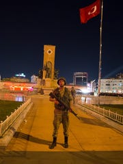 A soldier stands guard in front of a government building during a coup attempt in Turkey.