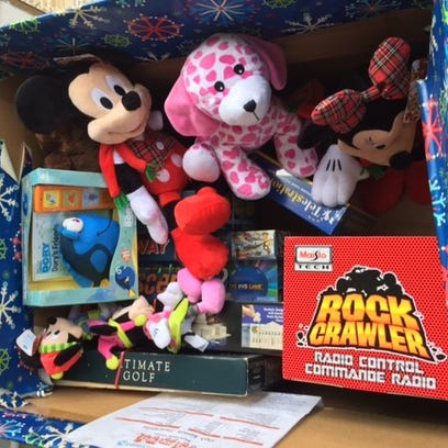 Donated toys are shown in a collection box outside