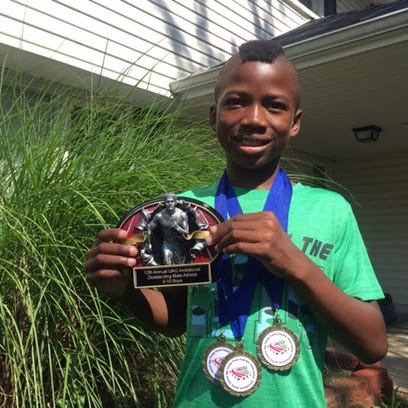 Zak'r Roberson with his three championship medals and