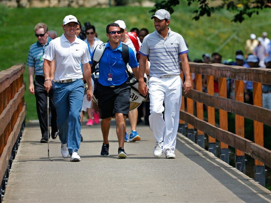 Rory McIlroy, of Northern Ireland, left, and Sergio Garcia, of Spain, walk along the foot bridge on the fourth hole during a practice round for the PGA Championship golf tournament at Valhalla Golf Club on Tuesday, Aug. 5, 2014, in Louisville, Ky. The tournament is set to begin on Thursday. (AP Photo/Mike Groll)