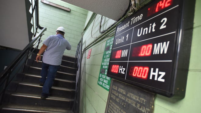 A display board shows no power output from Cabras Units 1 and 2 as Assistant Plant Superintendant Francis Cruz heads to the plant's second floor on Sept. 7.