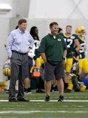 Brian Gutekunst and Mark Murphy watch practice.