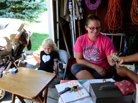Charity Pits, right, with her daughter, Ariel, 4, makes a sale at her Buckland Avenue garage sale on Friday afternoon.