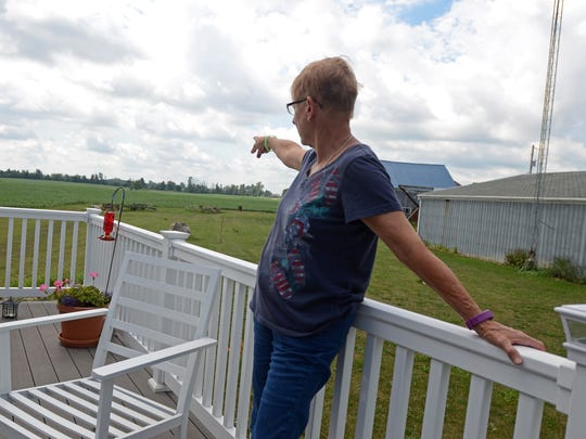 Mary Twiss points to an area that may one day have a wind turbine on it, Monday, July 25, at her home in Sanilac Township.