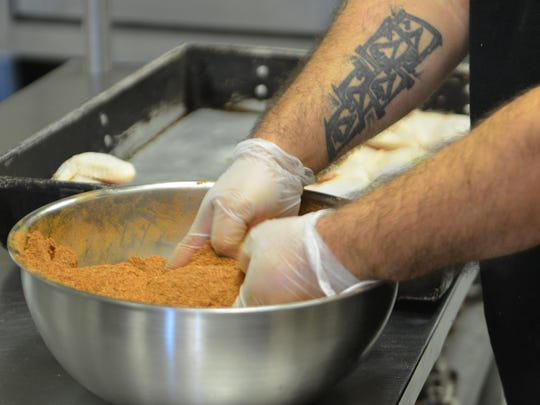 Zach Landt readies seasoning in the kitchen at Low N Slow's BBQ in Francis Creek.