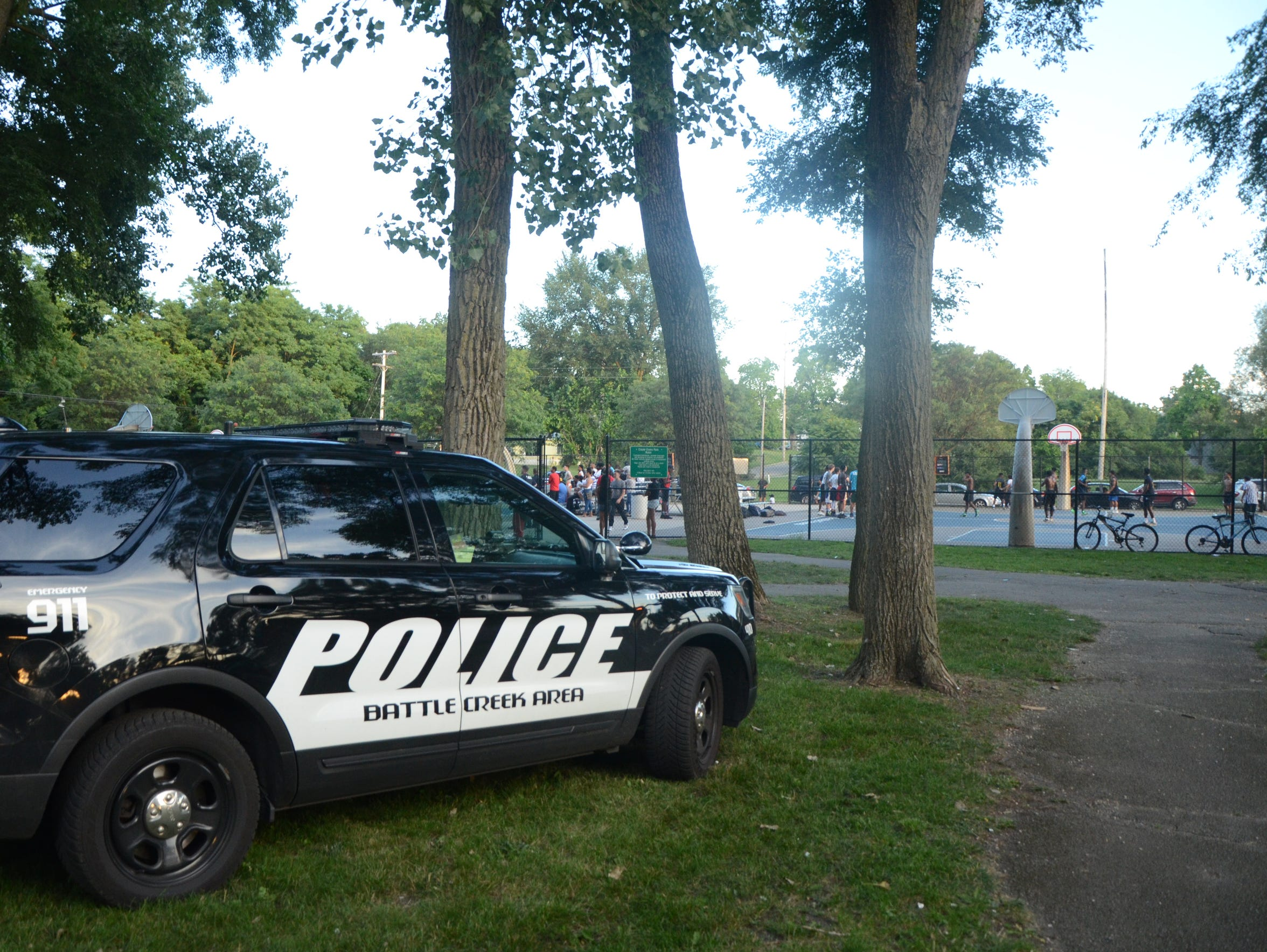 A police cruiser is parked on the grass outside of