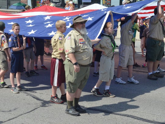 Local scouts carried a large American flag during the