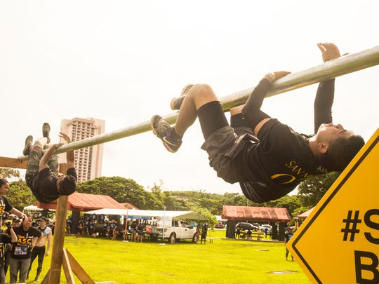 In this file photo, competitors shimmy across an obstacle at the 2017 Konqer obstacle course challenge.