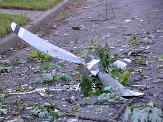 A propellor lies on the street under a tree that a small plane hit as it crashed on Milton Street, west of Van Dyke, near Detroit's city airport Sunday night.