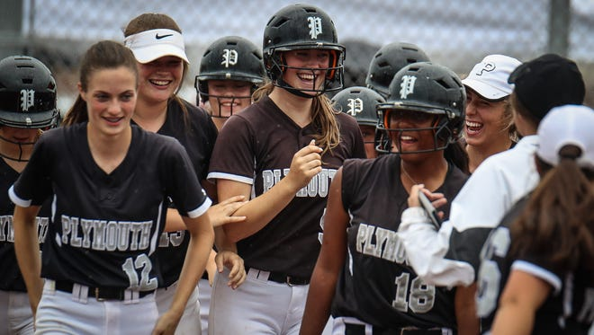 Plymouth senior Whitney Holden (5, center) is congratulated by happy teammates after hitting a grand slam against Allen Park.