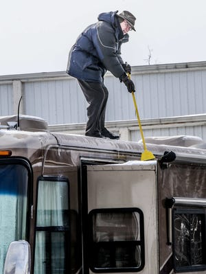 Charles Currey of Florida uses a broom Feb. 9, 2014, to brush snow and ice off of his motorhome. Currey and other purebred dog exhibitors and fans gathered at the Indiana State Fairgrounds for the Indy Winter Classic Dog Show.