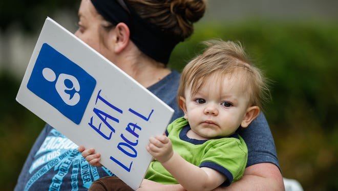 """James Bickel, 10 months, holds a sign for his mother Charla that reads """"eat local."""" The Bickels were among a group of protesting mothers with their spouses and children that gathered along Gilbert Avenue to challenge the idea of censoring breast feeding."""