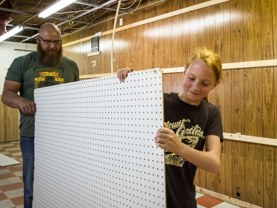 Riley Holsoppel, 12, helps her dad, Todd, move old peg board as construction for Red Canoe General Store at Leed's Corner and Mount Gretna Craft Brewery at Leed's Corner continued on Thursday, August 18, 2016.