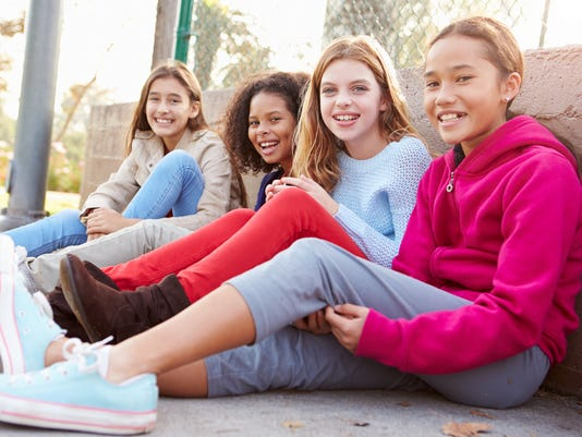 Four Young Girls Hanging Out Together In Park