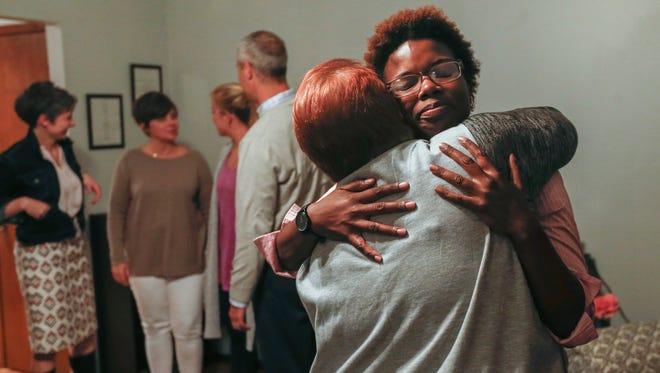 O'Brien Daniels hugs her friend Jayne Hewitt-Hood inside of her new home.