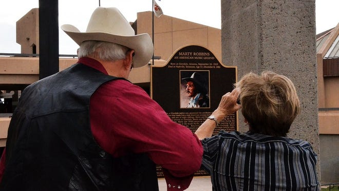 Bill and Marlene Vartus snap photos of a Marty Robbins plaque in nearby Murphy Park. The bronze plaque honoring Robbins was dedicated in 2014.